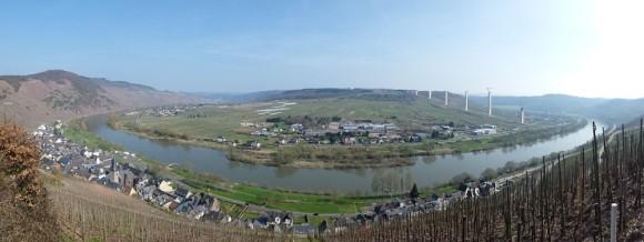 Die Baustelle der Hochmoselbrücke bei Ürzig (im Vordergrund) im April 2015. Auf 15 Stahlbetonpfeilern wird die Brücke die Mosel in rund 160 Metern Höhe überqueren.  Bild: Matthias H., Wikimedia (lizenzfrei)