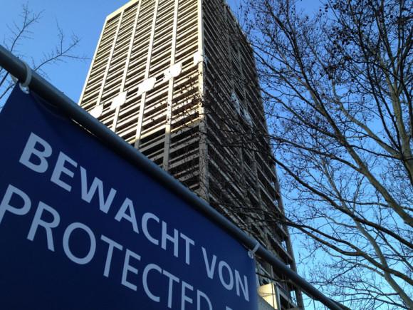 Ein Wachdienst hat ein Auge auf den Sprengstoff am Gebäude.