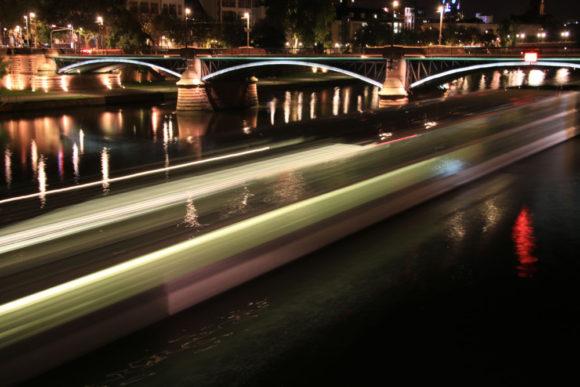 Ein Flusskreuzfahrtschiff verlässt das nächtliche Frankfurt und setzt seine Reise mainaufwärts fort.